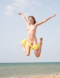 Beautiful blonde babe in arms jumping naked on the beach
