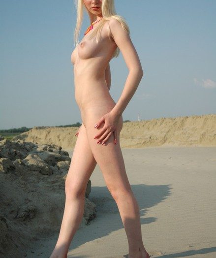 Young and beautiful blonde Aisha getting nude on the beach