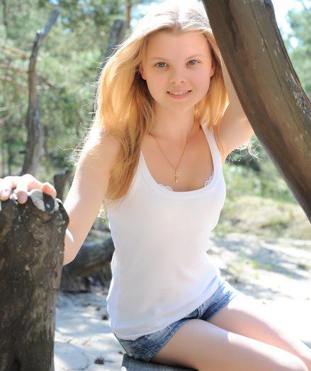 Teen posing between trees