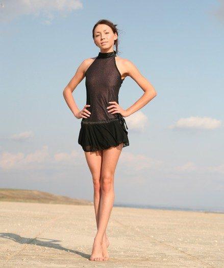 Tall skinny brunette taking off her transparent black raiment on the beach